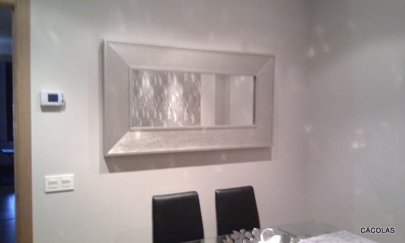 Espejo plata a juego con mueble de salón, sillas tapizadas en polipiel negra.