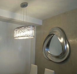 Zona de comedor , espejo plata , lámpara con cristales interiores.