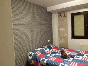 Habitación juvenil con papel pintado imitando adoquín gris.