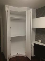 Detalle del interior del armario en rincón lacado en blanco.