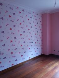 Detalle de papel pintado habitación infantil de corazones.