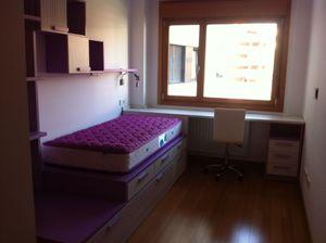 Habitación juvenil con cama en tatami, escritorio y estantería.
